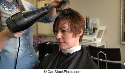 Stylist puts hair dryer and comb - Stylist dry and style...