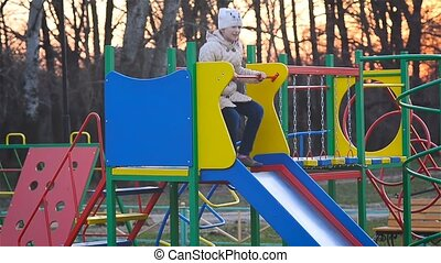 A child riding a roller coaster at the playground at sunset