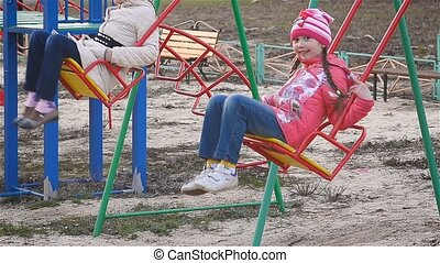 Children ride on a swing