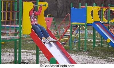 Girl riding a roller coaster at the playground - Little girl...