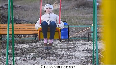 Girl riding on a swing in the playground is very highly...
