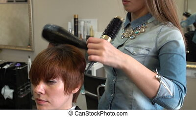 Hairdresser puts hair dryer and a round hairbrush - Stylist...