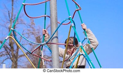 Girl climbs the ropes on the bright playground