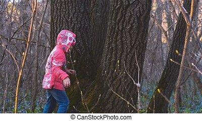 Girls in the forest running around tree