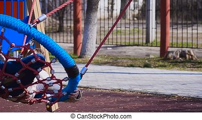 Girl swinging on a swing in the playground and smiling