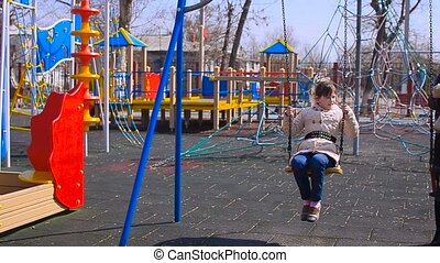 Girl swinging on a swing - Girl on a swing at playground and...