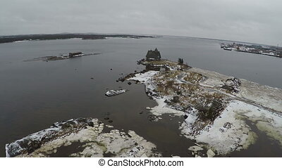 Flying over old wooden house in the sea - Aerial winter shot...