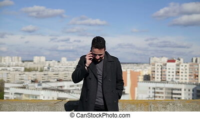 Man talking on the phone on the roof of the house. - Man...
