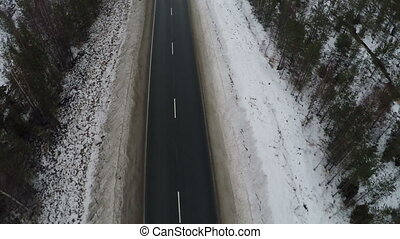 Aerial shot of empty winter road - Flying over the road with...