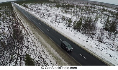 Aerial view of minivan driving winter road - Aerial view of...
