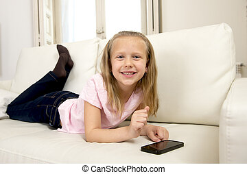 happy blond little girl on home sofa using internet app on...