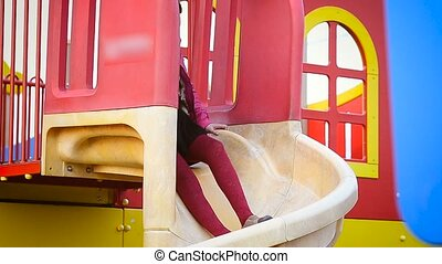 A girl riding a slide - A girl in a skirt riding on the...