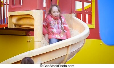 Girls riding a slide - Girl rides on the playground with...