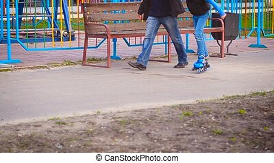 The child learns to ride on roller skates on a paved road in...