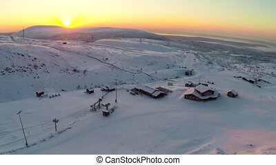 Flying over ski resort in the north at sunset