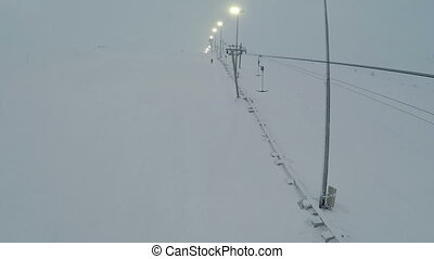 Aerial shot of ski lift and lampposts - Flying over the...