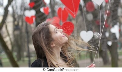 Stylish blonde girl playing with red paper hearts decoration in the autumn park. Valentine's day celebration