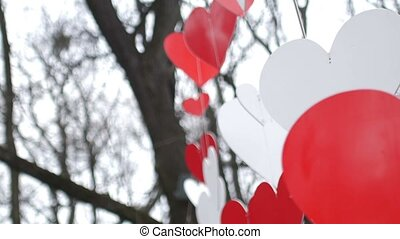 Love heart balloons on sky background. Paper red hearts decoration in the autumn park. Valentine's day concept