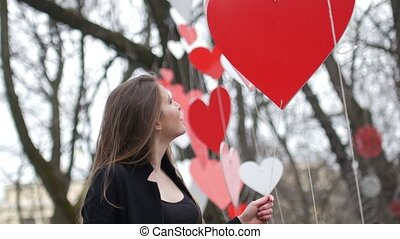 Beautiful young urban fashion girl plays with paper hearts decoration in the autumn park. Valentine's Day concept.