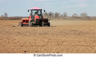 Red tractor seeding grain - Red tractor seeding grain in...