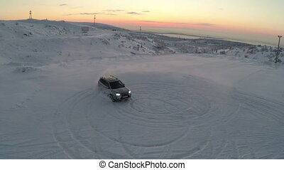 Flying over the car drifting on snow - Aerial shot of a car...