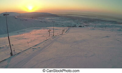 Ski-run and snowy hills at sunset, aerial view