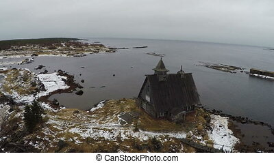 Wooden house at the edge of waterside, aerial view - Flying...