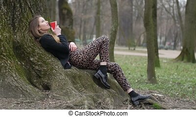Beautiful dreamy young hipster girl relying on the tree and...