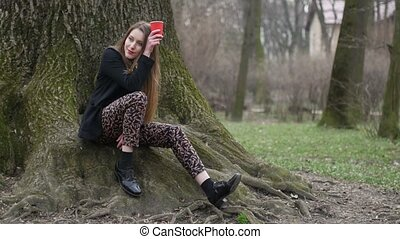Beautiful young hipster girl sitting by the leafless tree...