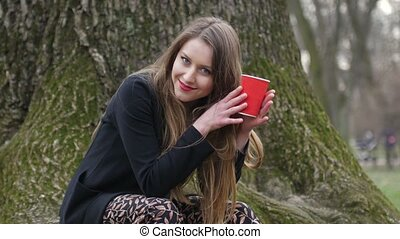 Young stylish blonde woman drinking coffee to go in the autumn park. Leafless tree on background