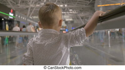 Little kid on flat escalator in trade center - Back view of...