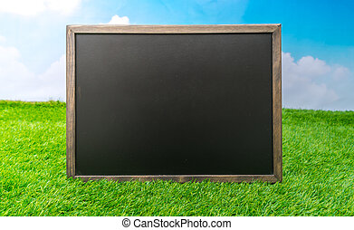 Blank black board on grass field