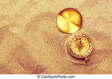 Top view of vintage compass in beach sand, navigational...