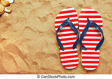 Pair of thongs or flip flops on beach sand, top view of...