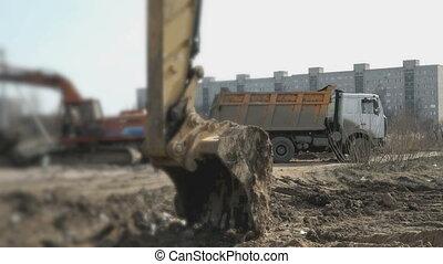 Excavator loads the clay into orange dump truck on...