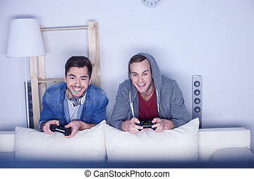 Attractive two guys are playing video games - Cheerful young...
