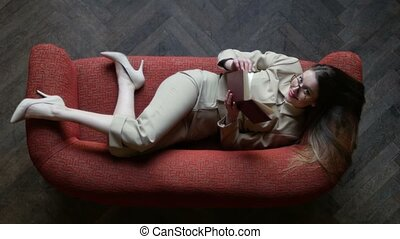 Attractive blond tattoed girl in glasses and beige suit...