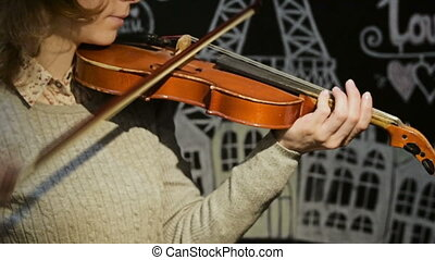 girl playing violin - girl in a gray jacket playing the...