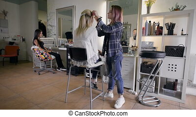 Picture of working day inside the beauty- sit on chair client beautiful young woman. Make-up artist doing make-up in a beauty salon.