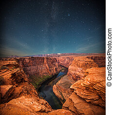 Grand Canyon at night under the light of the stars in the...