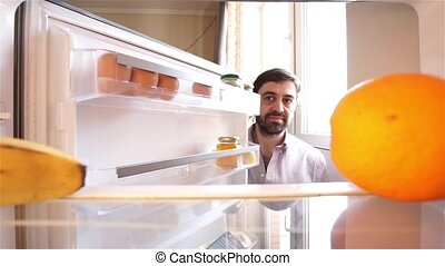 Hungry bearded man looking for food in refrigerator - Hungry...