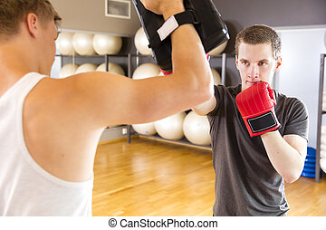 Two focused men training boxing at the fitness gym