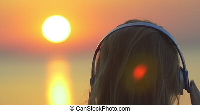 Woman enjoying music and sunset - Close-up back shot of a...