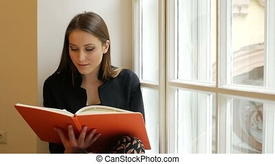 Beautiful dreamy young lady posing on the windowsill and reading a book