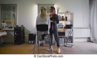 The friendly stylist working with his regular customer in a beauty salon. Attractive blonde woman