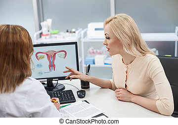 Beautiful blond girl is consulting with gynecologist -...