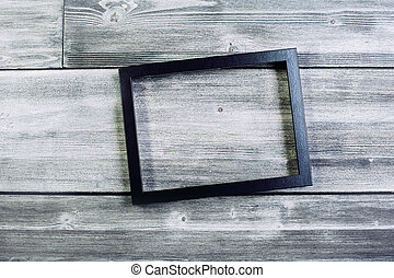 Black see-through frame on wooden wall. Mock up