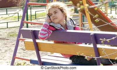 girl teen talking on phone smartphone in playground - girl...