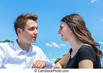 Young man and woman in love conversating with blue sky
