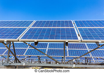 Metal frames with rows of blue solar collectors and sky -...